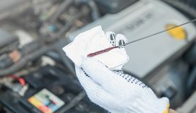 Technician checking oil level in car engine royalty free stock photo