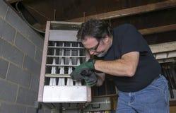 Technician Checking Out A Overhead Gas Furnace Stock Photos
