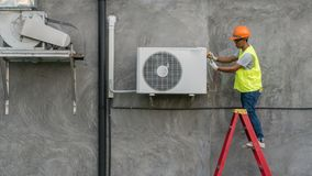 Technician is checking air conditioner. Technician is checking outdoor air conditioner unit stock images