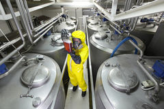 Technician checking technological process. Technician in protective uniform,mask,goggles,gloves and wellies checking technological process Stock Image