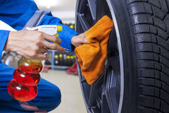 Technician cleaning a tire at workshop Stock Image