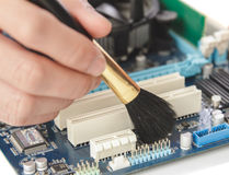 technician cleaning up the hardware of computer using brush Royalty Free Stock Photo