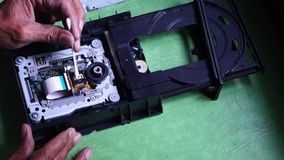 Technician cleans laser head or optical lens of DVD Hard Drive. Close up stock video footage