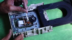 Technician cleans laser head or optical lens of DVD Hard Drive. Close up stock footage