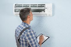 Technician with clipboard looking at air conditioner Stock Image