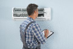 Technician with clipboard looking at air conditioner royalty free stock images
