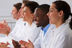 Technician And Colleagues In Laboratory Clapping Stock Photo