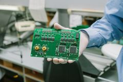 Technician with computer circuit board with chips. Spare parts and components for computer equipment. Production of. Electronics and maintenance Royalty Free Stock Photos