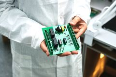 Technician with computer circuit board with chips. Spare parts and components for computer equipment. Production of. Electronics and maintenance. The concept of Royalty Free Stock Image
