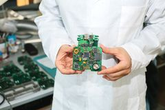 Technician with computer circuit board with chips. Spare parts and components for computer equipment. Production of. Electronics and maintenance. The concept of Stock Photography