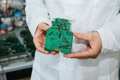Technician with computer circuit board with chips. Spare parts and components for computer equipment. Production of. Electronics and maintenance. The concept of Royalty Free Stock Photos