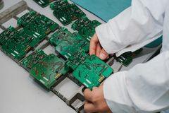 Technician with computer circuit board with chips. Spare parts and components for computer equipment. Production of. Electronics and maintenance. The concept of Royalty Free Stock Images