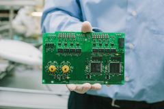Technician with computer circuit board with chips. Spare parts and components for computer equipment. Production of. Electronics and maintenance Stock Photography