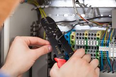 Technician cutting cable with fusebox in background Royalty Free Stock Image