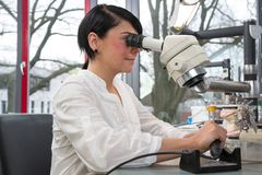 Technician in a dental lab or workshop working under a microscope Stock Images
