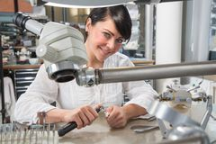 Technician in a dental lab or workshop working under a microscope Royalty Free Stock Photos