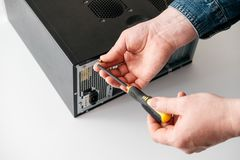 Technician disassemble computer with a screwdriver for problems diagnostic. And repair stock images