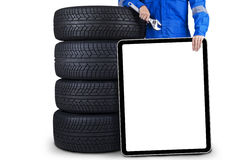 Technician with empty signboard. Mechanic person holding a wrench and empty signboard while standing next to a pile of tires Stock Image