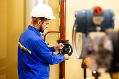Technician engineer closes gate valve on water pipeline in industrial factory. Maintenance of industry oil and gas plant royalty free stock photos