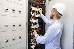 Technician engineer in datacenter. Network technician connecting fiber optic at server room. Technician engineer in datacenter. Network technician connecting royalty free stock image