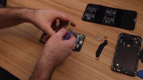 Technician or engineer disassembling components broken smartphone for repair or replace new smartphone battery on bamboo desk.  stock video footage