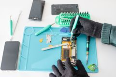 Technician or engineer disassembling components broken smartphone and take off logic board for repair or replace new smartphone royalty free stock photo
