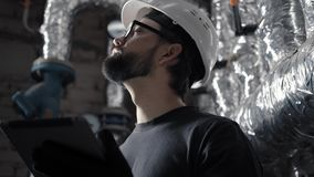 Technician engineer in a helmet works in a boiler room with a tablet