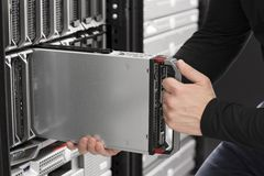IT Engineer insert a Blade Server in Data Center. IT technician / engineer install / removes / replace a blade server in a data center Royalty Free Stock Images
