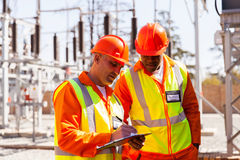 Technician and engineer. Professional senior technician and electrical engineer writing on clipboard in substation Stock Photography