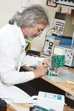 Technician engineer at work with microchip. Male technicial engineer with microchip plate at test laboratory factory Royalty Free Stock Photography