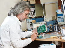 Technician engineer at work with microchip. Male technicial engineer with microchip plate at test laboratory factory Royalty Free Stock Photos