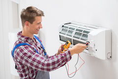 Technician Examining Air Conditioner. Male Technician Examining Air Conditioner With Multimeter Stock Photos