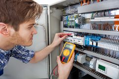 Technician examining fusebox with insulation resistance tester royalty free stock photo