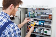 Technician examining fusebox with insulation resistance tester Royalty Free Stock Photography