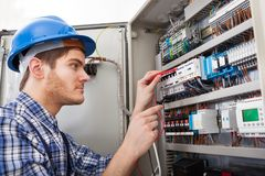 Technician examining fusebox with multimeter probe Royalty Free Stock Images