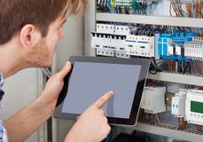 Technician examining fusebox using tablet Royalty Free Stock Photos