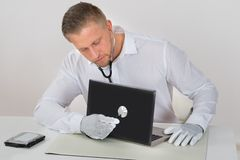 Technician Examining Laptop With Stethoscope Royalty Free Stock Photos