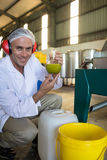 Technician examining olive oil produced from machine. In factory Stock Images