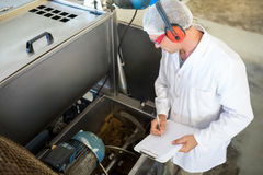 Technician examining processing machine. In oil factory Royalty Free Stock Photo