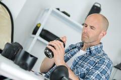 Technician examining and repairing dslr camera. Man Stock Images