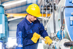 Technician in factory at machine maintenance Stock Image