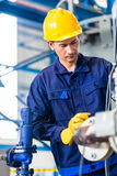 Technician in factory at machine maintenance. Technician in Asian factory at machine maintenance working with wrench Stock Image