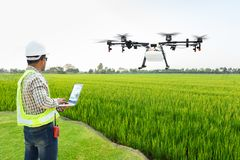 Technician farmer use wifi computer control agriculture drone fly to sprayed fertilizer on the rice fields, Smart farm 4.0 concept.  stock photo