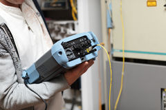 Technician with fibre optic analyser. Telecom technician holding fibre optic analyser at server room Stock Images