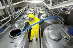 Technician filling large silver tank in factor Royalty Free Stock Photos
