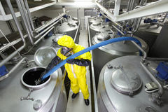 Technician filling large  silver tank in factory Stock Photo
