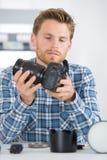 Technician fitting camera lens to body. Camera Stock Photos
