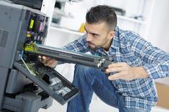 Technician fix printer by screwdriver. Technician fix the printer by screwdriver Stock Photo
