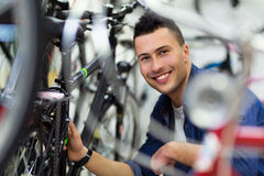Technician fixing bicycle in repair shop Royalty Free Stock Photos