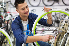 Technician fixing bicycle in repair shop Royalty Free Stock Photography